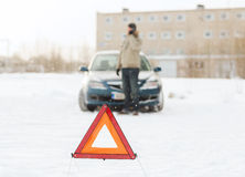 Closeup of man with broken car and smartphone. Transportation, winter and vehicle concept - closeup of man with broken car, warning triangle and smartphone Stock Image