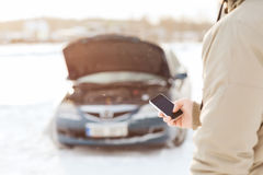 Closeup of man with broken car and smartphone. Transportation, winter and vehicle concept - closeup of man with broken car and smartphone stock photo