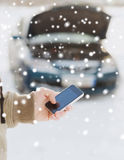 Closeup of man with broken car and smartphone. Transportation, winter, people and vehicle concept - closeup of man with broken car and cell phone Royalty Free Stock Photos