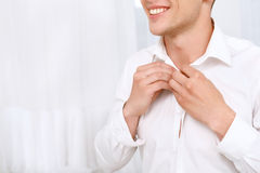 Closeup of man buttoning up to neck shirt Stock Photos