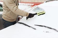 Closeup of man cleaning snow from car Stock Photos