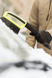 Closeup of man cleaning snow from car Stock Images