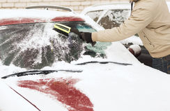 Closeup of man cleaning snow from car Stock Photos