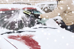 Closeup of man cleaning snow from car Stock Photo