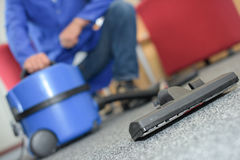 Closeup man crouching by vacuum cleaner Stock Image