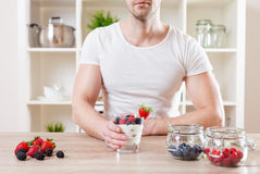 Closeup on man with delicious yoghurt with fresh berries. Healthy eating concept. Closeup on man with delicious yoghurt with fresh berries stock images
