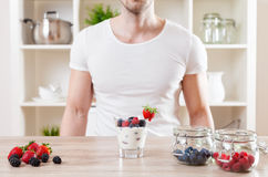 Closeup on man with delicious yoghurt with fresh berries. Healthy eating concept. Closeup on man with delicious yoghurt with fresh berries royalty free stock photography