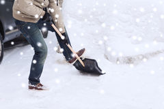 Closeup of man digging snow with shovel near car. Transportation, winter, people and vehicle concept - closeup of man digging snow with shovel near car stock photo