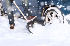 Closeup of man digging snow with shovel near car Stock Photos
