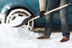 Closeup of man digging up stuck in snow car Stock Image