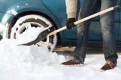 Closeup of man digging up stuck in snow car Stock Image