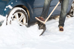 Closeup of man digging up stuck in snow car Royalty Free Stock Photography