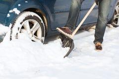 Closeup of man digging up stuck in snow car Royalty Free Stock Photography