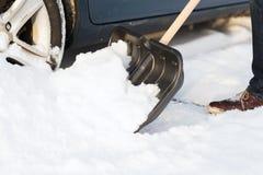 Closeup of man digging up stuck in snow car Royalty Free Stock Photo