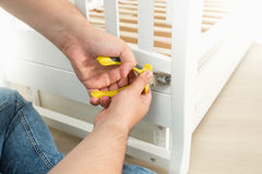 Closeup of man disassembling white wooden bed stock images