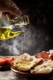 Catalan pa amb tomaquet with serrano ham. Closeup of a man dressing with olive oil some slices of typical catalan pa amb tomaquet, bread with tomato, placed on a Royalty Free Stock Image