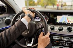 Closeup of man driving a car holding steering wheel. Turning right Royalty Free Stock Images