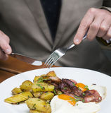 Closeup of man eating fried eggs, potatoes and bacon Royalty Free Stock Photo