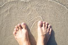 Closeup man feet standing on sea sand with relaxing time feeling in the holiday. Closeup man feet standing on sea sand with relaxing time feeling royalty free stock images