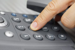 Closeup of man finger is dialing a telephone number.  Stock Photos