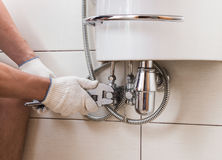 Closeup man fixing sink in a bathroom royalty free stock photography