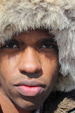 Closeup of a Man with a Fur Cap. A close up shot of a black man with his face framed by a fur hat Royalty Free Stock Photos