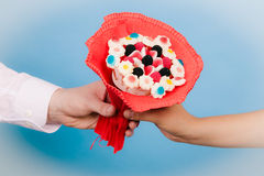 Closeup of man giving woman candy bunch flowers. Royalty Free Stock Image