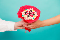 Closeup of man giving woman candy bunch flowers. Closeup of men giving women candy bunch flowers. Boyfriend holding present gift for girlfriend. Love Royalty Free Stock Images