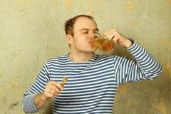 Closeup of a man with a glass of beer. Closeup of a young man with a beer and dried fish. The guy on the background of the old concrete wall in white and blue stock photos