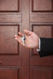 Closeup on man hand holding keys to apartment door. Stock Photo