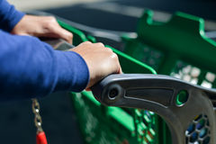 Closeup of man hand with shopping cart. Closeup picture of male hand holding shopping push cart on car parking Royalty Free Stock Photos