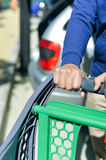 Closeup of man hand with shopping cart. Closeup picture of male hand holding shopping push cart on car parking Royalty Free Stock Photography