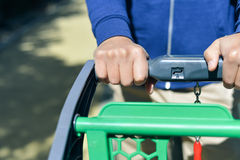 Closeup of man hand with shopping cart. Closeup picture of male hand holding shopping push cart on car parking Royalty Free Stock Images