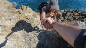 Closeup of man hand helping female friend climb the mountain top