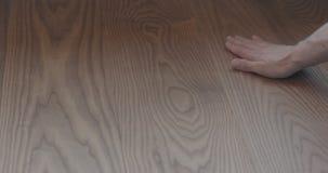Closeup man hand touches ash wood floor. Shallow focus stock photo