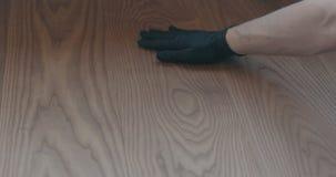 Closeup man hand touches ash wood floor. Shallow focus stock photography