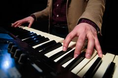 Playing keyboard. Closeup of a man hands playing a piano or keyboard royalty free stock images