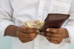 Closeup of Man hands taking Indian currency out of his wallet royalty free stock images
