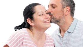 Closeup of man kissing woman cheek. Closeup of smiling men kissing women cheek as couple concept isolated on white studio background royalty free stock images