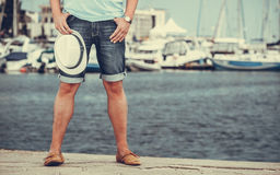 Closeup of man legs on pier in port with yachts. Royalty Free Stock Photos