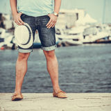 Closeup of man legs on pier in port with yachts. Stock Photo