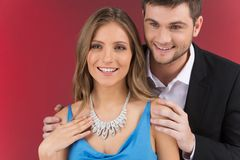 Closeup on man looking at necklace on girl's neck Stock Photography