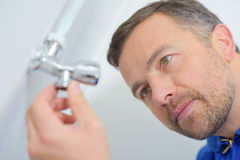 Closeup man looking at radiator tap Stock Photography