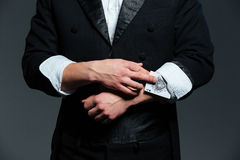 Closeup of man magician with ace in his sleeve. Closeup of man magician in balck tail coat with ace in his sleeve over grey background Royalty Free Stock Photography
