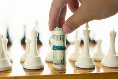 Closeup of man making move in chess game with twisted banknotes Royalty Free Stock Photos