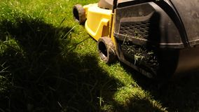 Closeup of a man mowing the grass with lawn mower. stock video footage