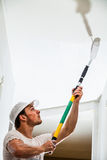 Closeup of Man Painting the Ceiling. Closeup of Man Holding Roller Pin and Painting the Ceiling stock photography