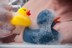 Man playing with rubber duck toys on bath Royalty Free Stock Image