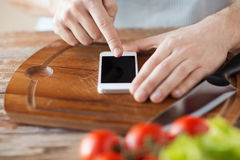 Closeup of man pointing finger to smartphone Stock Image
