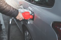 Closeup of man pumping gasoline fuel in car at gas station. Royalty Free Stock Images